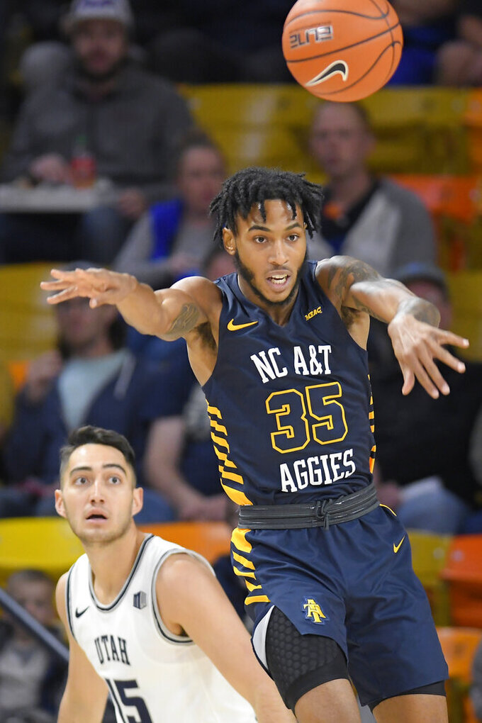 North Carolina A&T forward Tyrone Lyons (35) passes the ball as Utah State guard Abel Porter (15) defends during the first half of an NCAA college basketball game Friday, Nov. 15, 2019, in Logan, Utah. (AP Photo/Eli Lucero)