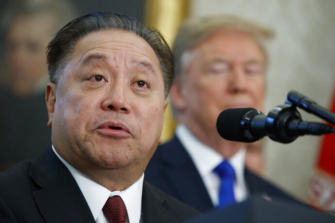 FILE - In this Nov. 2, 2017, file photo, Broadcom CEO Hock Tan speaks as President Donald Trump listens during an event to announce the company is moving its global headquarters to the United States, in the Oval Office of the White House, in Washington. Broadcom's shares fell on Friday, June 14, 2019, along with those of other chipmakers, after the company lowered revenue guidance for the rest of the year due to trade tensions and a