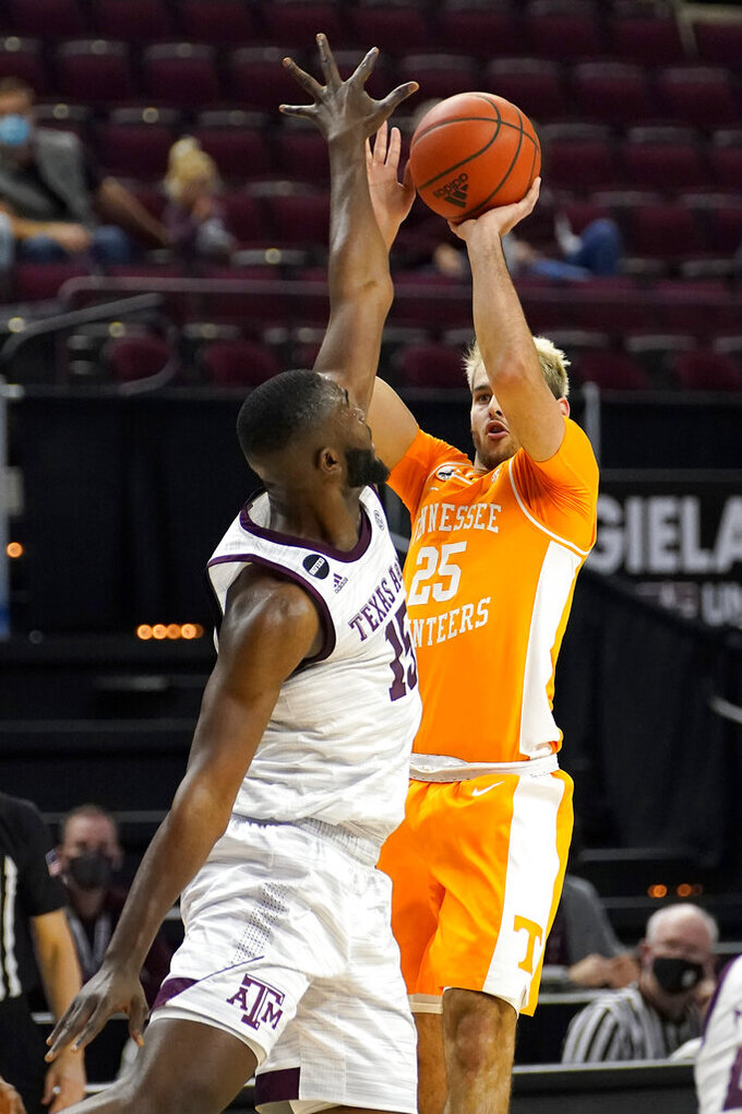 Tennessee guard Santiago Vescovi (25) makes a 3-point basket over Texas A&M forward Jonathan Aku (15) during the first half of an NCAA college basketball game Saturday, Jan. 9, 2021, in College Station, Texas. (AP Photo/Sam Craft)