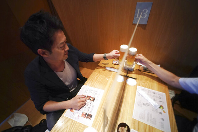Customers drink a toast through plastic partitions at Kichiri, an
