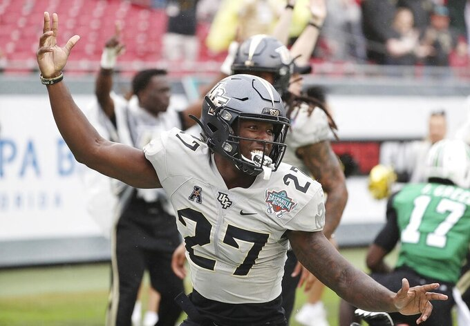 Central Florida defensive back Richie Grant (27) celebrates his interception return for a touchdown against Marshall during the Gasparilla Bowl NCAA college football game Monday, Dec. 23, 2019, in Tampa, Fla. (Stephen M. Dowell/Orlando Sentinel via AP)