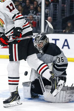 Los Angeles Kings goalie Jack Campbell (36) stops a shot next to Chicago Blackhawks forward Dylan Strome (17) during the first period of an NHL hockey game Saturday, March 30, 2019, in Los Angeles. (AP Photo/Ringo H.W. Chiu)