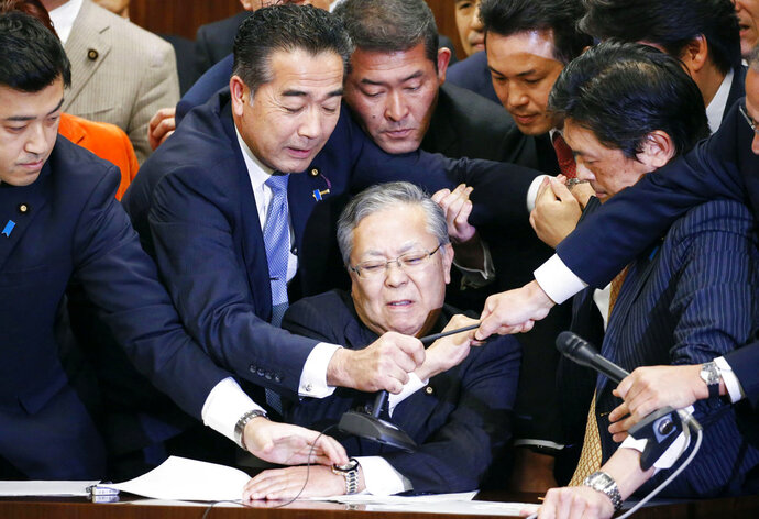 Japan's ruling parties and opposition parties' members scramble for a microphone as opposition parties try to stop Judicial Affairs Committee Chairman Shinichi Yokoyama, bottom center, from moving to hold a vote for a bill to revise an immigration control law, at upper house committee in Tokyo early Saturday, Dec. 8, 2018. Japan is preparing to officially open the door to foreign workers to do unskilled jobs and possibly eventually become citizens. (Toshiyuki Matsumoto/Kyodo News via AP)