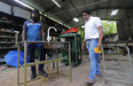 In this June 12, 2020 photo, Sri Lankan entrepreneur Nishantha Abeyrathne, right, checks a paddle sink that is made at his workshop in Paththanduwana village in Sri Lanka. Abeyrathne's company seized upon an opportunity when factories in Sri Lanka were allowed to reopen; the government required owners to install sinks so employees could wash their hands, and Abeyrathne designed one with a foot paddle so workers wouldn't have to touch the faucet.    (AP Photo/Eranga Jayawardena)