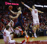 Illinois' Giorgi Bezhanishvili (15) fouls Wisconsin's Nate Reuvers (35) during the first half of an NCAA college basketball game Monday, Feb. 18, 2019, in Madison, Wis. At right is Wisconsin's Ethan Happ. (AP Photo/Andy Manis)