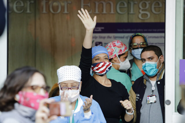 A medical worker waves to people cheering outside of NYU Langone Medical Center at 7 p.m., Tuesday, May 19, 2020, in New York, amid the coronavirus pandemic. (AP Photo/Frank Franklin II)