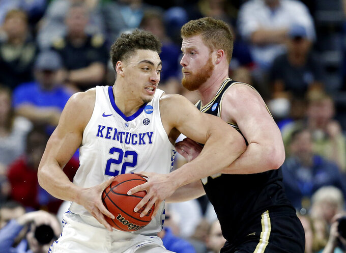 Kentucky's Reid Travis (22) goes in for a shot against Wofford's Matthew Pegram during the first half of a second-round game in the NCAA men's college basketball tournament in Jacksonville, Fla., Saturday, March 23, 2019. (AP Photo/Stephen B. Morton)
