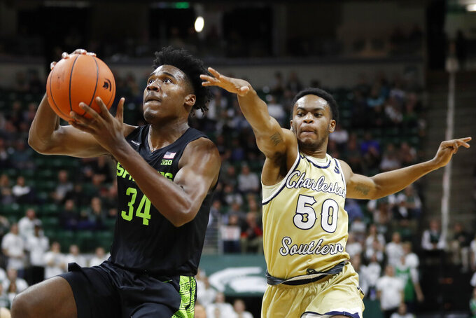 Michigan State forward Julius Marble (34) makes a layup as Charleston Southern guard Malik Battle (50) defends during the second half of an NCAA college basketball game, Monday, Nov. 18, 2019, in East Lansing, Mich. (AP Photo/Carlos Osorio)