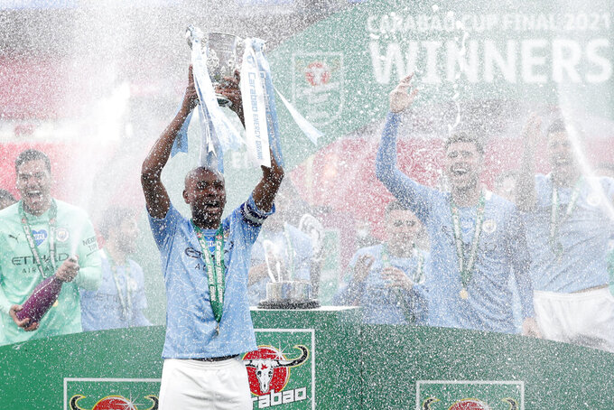 Manchester City's team captain Fernandinho lifts the trophy at the end of the English League Cup final soccer match between Manchester City and Tottenham Hotspur at Wembley stadium in London, Sunday, April 25, 2021. Manchester City won 1-0. (AP Photo/Alastair Grant)
