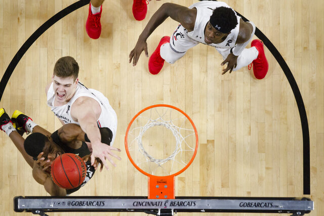 Cincinnati center Chris Vogt blocks Central Florida forward Collin Smith (35) during the first overtime of an NCAA college basketball game Wednesday, Feb. 19, 2020, in Cincinnati. (Albert Cesare/The Cincinnati Enquirer via AP)