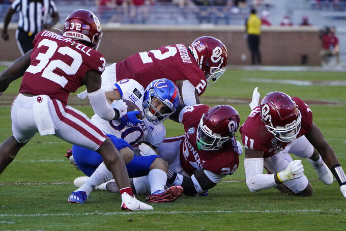 Kansas wide receiver Luke Grimm (80) is surrounded by Oklahoma's Delarrin Turner-Yell (32), David Ugwoegbu (2), Brian Asamoah (24) and Nik Bonitto (11) in the first half of an NCAA college football game in Norman, Okla., Saturday, Nov. 7, 2020. (AP Photo/Sue Ogrocki)