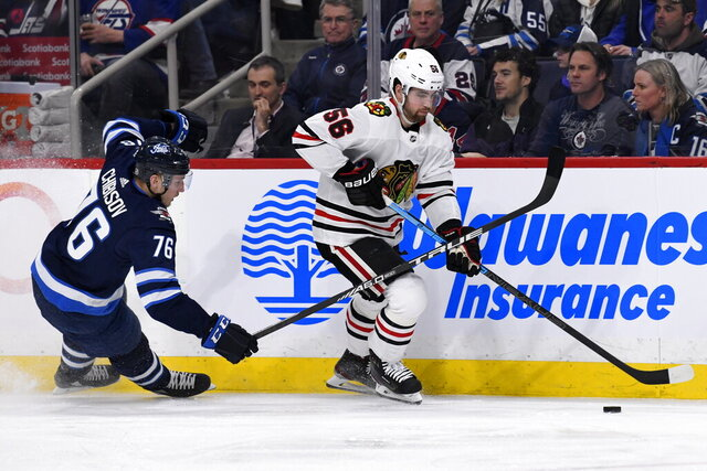 Chicago Blackhawks' Erik Gustafsson (56) skates away from Winnipeg Jets' Jacob Cederholm (78) during the second period of an NHL hockey game Sunday, Feb. 16, 2020, in Winnipeg, Manitoba. (Fred Greenslade/The Canadian Press via AP)