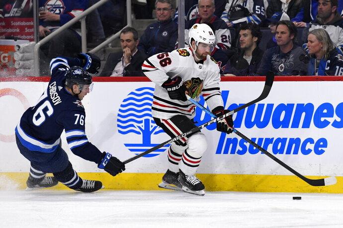 Chicago Blackhawks' Erik Gustafsson (56) skates away from Winnipeg Jets' Jacob Cederholm (78) during the second period of an NHL hockey game Sunday, Feb. 16, 2020, in Winnipeg, Manitoba. (Fred Greenslade/The Canadian Press via AP)