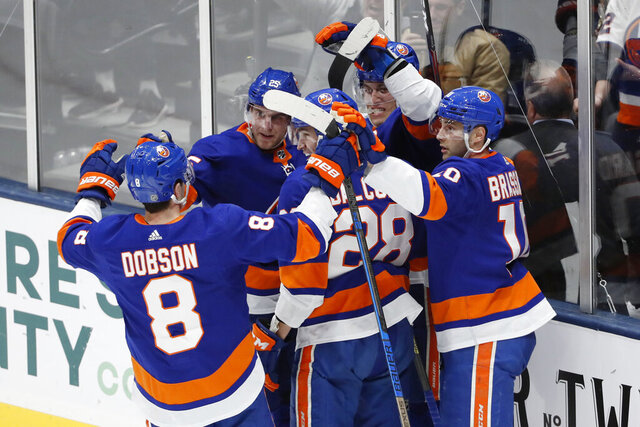 New York Islanders left wing Anders Lee (27), second from right with his back against the glass, celebrates with teammates, including defenseman Noah Dobson (8), left wing Michael Dal Colle (28), and center Derick Brassard (10) after scoring a goal during the third period of an NHL hockey game, Monday, Jan. 6, 2020, in Uniondale, N.Y. The Islanders defeated the Avalanche 1-0 on Lee's game-winning goal. (AP Photo/Kathy Willens)