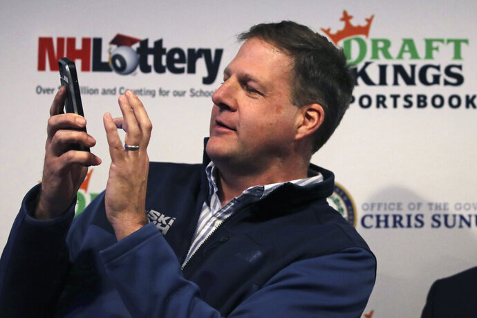New Hampshire Gov. Chris Sununu places the first legal sports wagering bet on his mobile phone for the New England Patriots to win the Super Bowl at a sports bar in Manchester, N.H., Monday, Dec. 30, 2019. New Hampshire, who partnered with DraftKings, is the second New England state to approve sports wagering. (AP Photo/Charles Krupa)