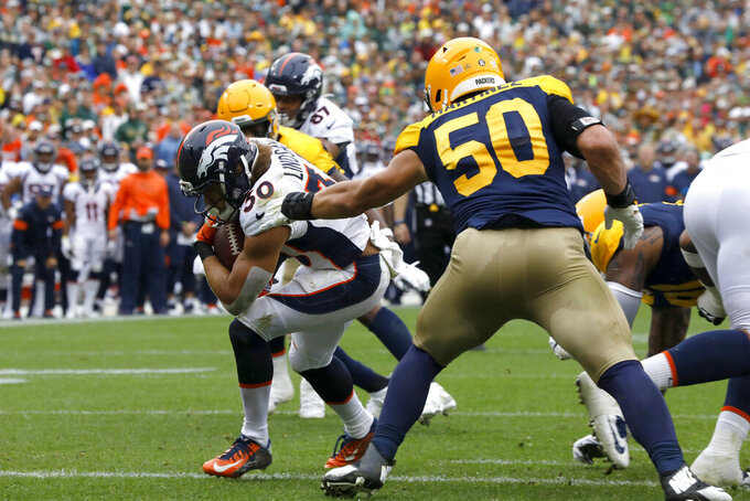 Denver Broncos running back Phillip Lindsay (30) scores past Green Bay Packers inside linebacker Blake Martinez (50) during the first half of an NFL football game Sunday, Sept. 22, 2019, in Green Bay, Wis. (AP Photo/Mike Roemer)
