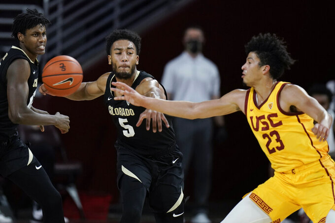 Colorado's D'Shawn Schwartz, left, tries to steal the ball from Southern California's Max Agbonkpolo during the first half of an NCAA college basketball game Thursday, Dec. 31, 2020, in Los Angeles. (AP Photo/Jae C. Hong)
