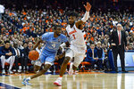 North Carolina guard Brandon Robinson, left, is defended by Syracuse forward Quincy Guerrier during the second half of an NCAA college basketball game in Syracuse, N.Y., Saturday, Feb. 29, 2020. North Carolina defeated Syracuse 92-79. (AP Photo/Adrian Kraus)