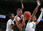 Iowa's Luka Garza, center, looks for a shot between Michigan State's Marcus Bingham Jr., left, and Malik Hall (25) during the first half of an NCAA college basketball game, Tuesday, Feb. 25, 2020, in East Lansing, Mich. (AP Photo/Al Goldis)