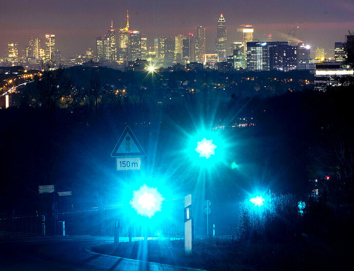 Green traffic lights shine above the city of Frankfurt, Germany, Tuesday, Feb. 5, 2019. (AP Photo/Michael Probst)