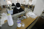 Yemeni women work to manufacture protective face masks, that are in high demand worldwide due the outbreak of the coronavirus, at a textile factory in Sanaa, Yemen, Tuesday, Mar. 17, 2020. For most people, the virus causes only mild or moderate symptoms. For some it can cause more severe illness. (AP Photo/Hani Mohammed)