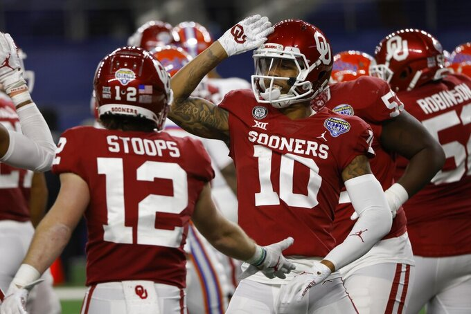 Oklahoma wide receivers Drake Stoops (12) and Theo Wease (10) celebrate a touchdown scored by Wease in the first half against Florida in the Cotton Bowl NCAA college football game in Arlington, Texas, Wednesday, Dec. 30, 2020. (AP Photo/Ron Jenkins)