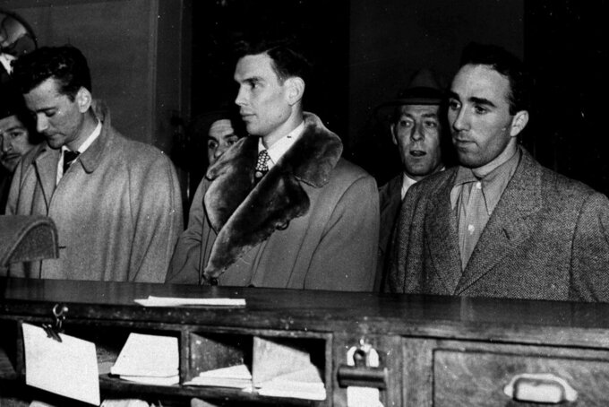 """FILE - In this March 27, 1951, file photo, three City College of New York basketball players, from left, Norman Mager, Irwin Dambrot and Herb Cohen are booked at New York's Elizabeth Street police station in connection with fixing of three basketball games at Madison Square Garden in 1949 and 1950. Mager and Dambrot last played during 1949-50 season and Cohen was a member of the 1950-51 CCNY squad. """"They were kings of the town one day, and the next day they were the bums of the town, really, because of the scandal,"""" said Dambrot's nephew, Duquesne coach Keith Dambrot. (AP Photo/File)"""