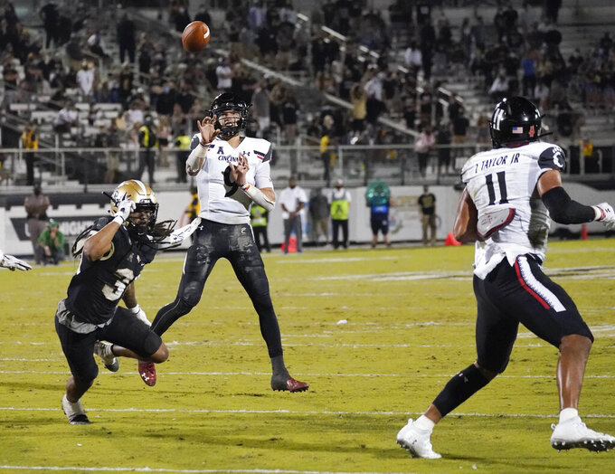 Cincinnati quarterback Desmond Ridder, center, throws a 7-yard touchdown pass to tight end Leonard Taylor (11) over Central Florida defensive back Aaron Robinson, left, during the second half of an NCAA college football game, Saturday, Nov. 21, 2020, in Orlando, Fla. (AP Photo/John Raoux)