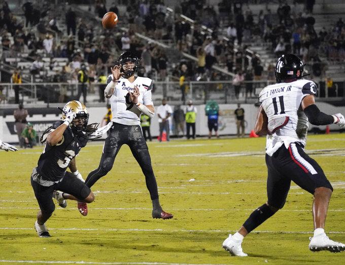 Cincinnati quarterback Desmond Ridder, center, throws a 7-yard touchdown pass to tight end Leonard Taylor (11) over Central Florida defensive back Aaron Robinson, left, during the second half of an NCAA college football game, Saturday, Nov. 21, 2020, in Orlando, Fla. (AP Photo/John Raoux)