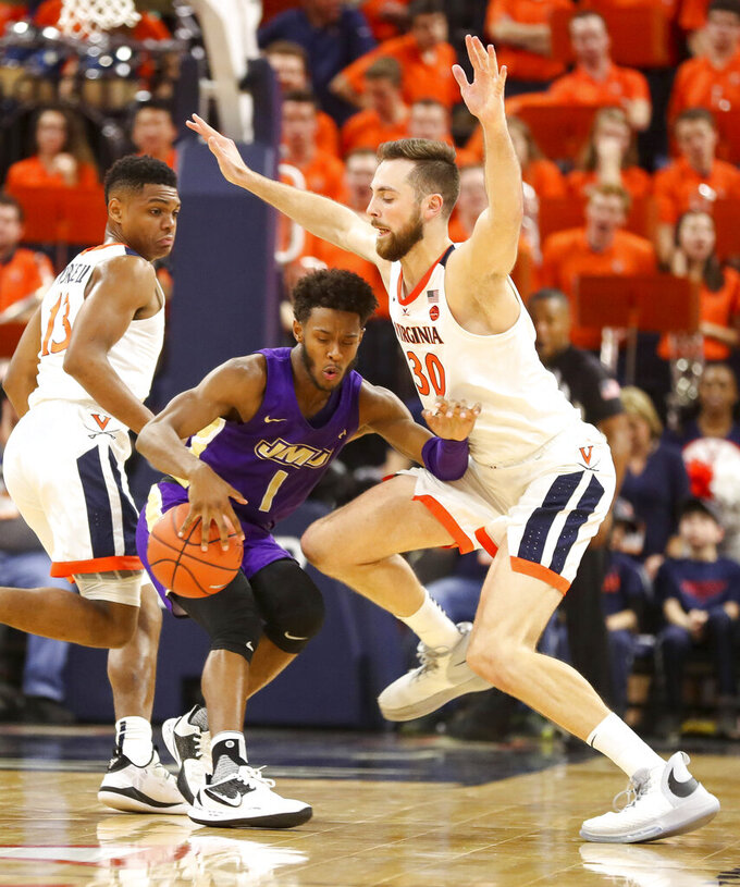 James Madison guard Matt Lewis (1) runs into the defense of Virginia forward Jay Huff (30) during an NCAA college basketball game in Charlottesville, Va., Sunday, Nov. 10, 2019. (AP Photo/Andrew Shurtleff)
