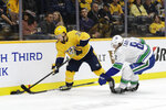 Nashville Predators right wing Viktor Arvidsson (33), of Sweden, battles for the puck with Vancouver Canucks defenseman Christopher Tanev (8) in the second period of an NHL hockey game Thursday, Nov. 21, 2019, in Nashville, Tenn. (AP Photo/Mark Humphrey)
