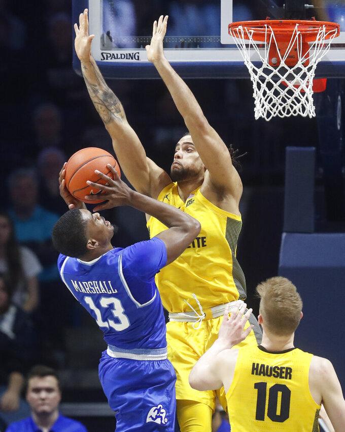 Xavier's Naji Marshall (13) shoots against Marquette's Theo John, center, in the second half of an NCAA college basketball game, Saturday, Jan. 26, 2019, in Cincinnati. (AP Photo/John Minchillo)