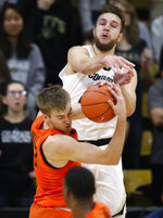 Oregon State forward Tres Tinkle, front, wrestles away a rebound from Colorado forward Lucas Siewert in the first half of an NCAA college basketball game Thursday, Jan. 31, 2019, in Boulder, Colo. (AP Photo/David Zalubowski)