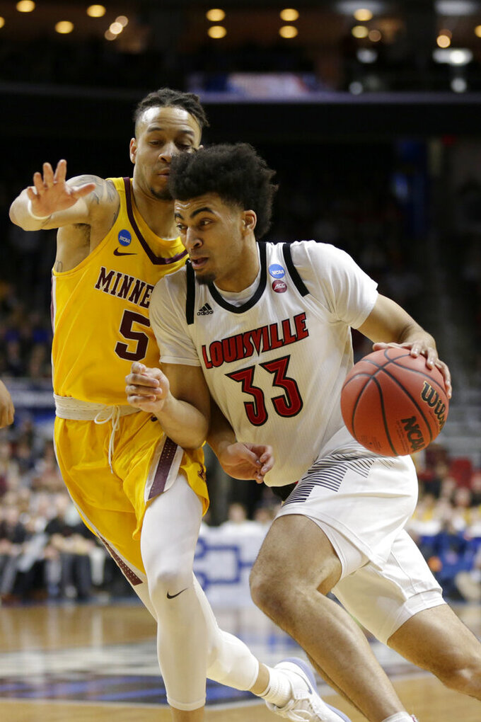 Louisville's Jordan Nwora (33) drives to the basket past Minnesota's Amir Coffey (5) during the first half of a first round men's college basketball game in the NCAA Tournament, in Des Moines, Iowa, Thursday, March 21, 2019. (AP Photo/Nati Harnik)