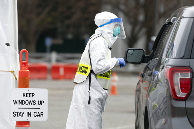 A medical worker screens people arriving at a special COVID-19 testing site in Boston, Saturday, March 28, 2020. The drive-thru testing site is only open to qualified first responders who meet the state criteria for testing. The new coronavirus causes mild or moderate symptoms for most people, but for some, especially older adults and people with existing health problems, it can cause more severe illness or death. (AP Photo/Michael Dwyer)