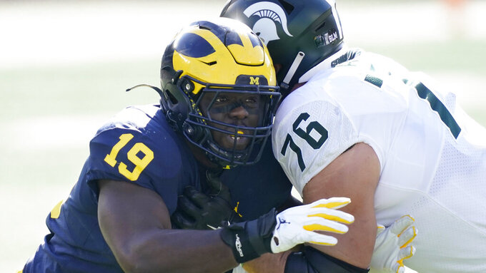 File-This Oct. 31, 2020, file photo shows Michigan defensive lineman Kwity Paye (19) rushing the quarterback during the first half of an NCAA college football game against Michigan State in Ann Arbor, Mich. Paye is one of the top edge rushers in this year's draft who could entice the Vikings with the No. 14 overall pick. (AP Photo/Carlos Osorio, File)