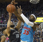 Nevada forward Caleb Martin (10) and New Mexico forward Carlton Bragg (35) go for a rebound in the first half of an NCAA college basketball game in Reno, Nev., Saturday, Feb. 9, 2019. (AP Photo/Tom R. Smedes)