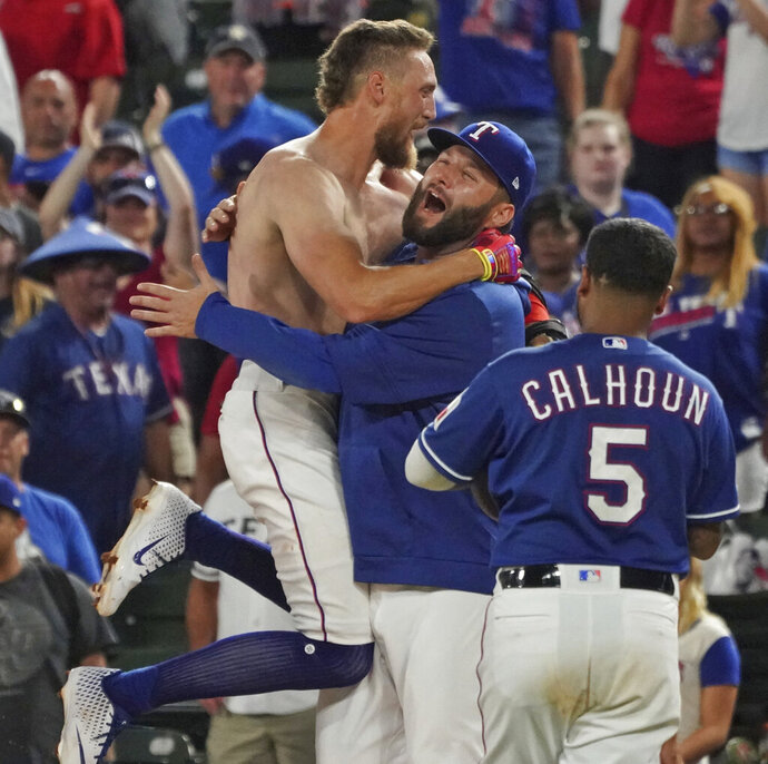 Texas Rangers' Hunter Pence is hugged by teammate Lance Lynn after driving in the winning run in the team's 8-7 win over the Los Angeles Angels in a baseball game Wednesday, Aug. 21, 2019, in Arlington, Texas. (AP Photo/Louis DeLuca)