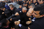 Bodyguards protect Kemal Kilicdaroglu, the leader of Turkey's main opposition Republican People's Party, as a man throws a punch toward him, during the funeral of a soldier who was slain during clashes with Kurdish rebels at Iraq border, outside Ankara, Turkey, Sunday, April 21, 201. The politician was not hurt, party officials said. Protestors at a village outside of Ankara threw punches at Kemal Kilicdaroglu as security officials tried to escort him away from the crowd, television footage showed. (DHA via AP Photo)