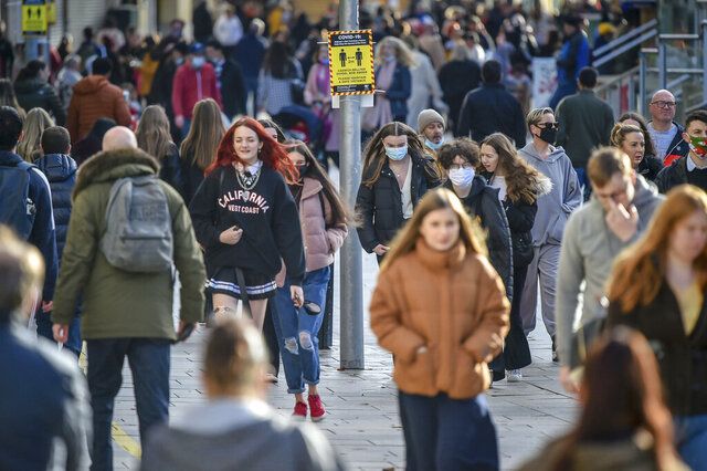 People pass a social distancing sign in Cardiff, where restrictions across Wales have been relaxed following a two-week