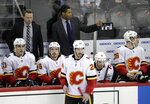 Calgary Flames assistant coach Paul Jerrard, top right, stands next to head coach Glen Gulutzan, top left, during the third period of an NHL hockey game against the New Jersey Devils, Thursday, Feb. 8, 2018, in Newark, N.J. The NHL has almost two dozen black players but just one black official in linesman Shandor Alphonso and one black coach in Flames assistant Paul Jerrard. (AP Photo/Julio Cortez)