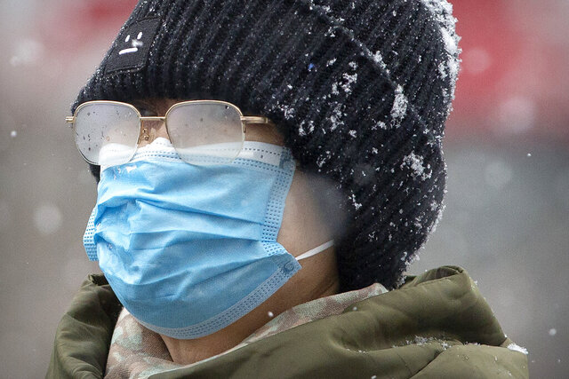 A woman's eyeglasses are fogged up as she wears a face mask during a snowfall in Beijing, Sunday, Feb. 2, 2020. China's death toll from a new virus increased to 304 on Sunday amid warnings from the World Health Organization that other countries need to prepare in the event the disease spreads among their populations as more nations report local infections. (AP Photo/Mark Schiefelbein)