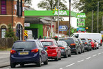 Cars queue outside a petrol station in Reading, England, Saturday Sept. 25, 2021. The haulage industry says the U.K. is short tens of thousands of truckers, due to a perfect storm of factors including the coronavirus pandemic, an aging workforce and an exodus of European Union workers following Britain's departure from the bloc. BP and Esso shut a handful of their gas stations this week, and motorists have formed long lines as they try to fill up in case of further disruption.  Steve Parsons/PA via AP)