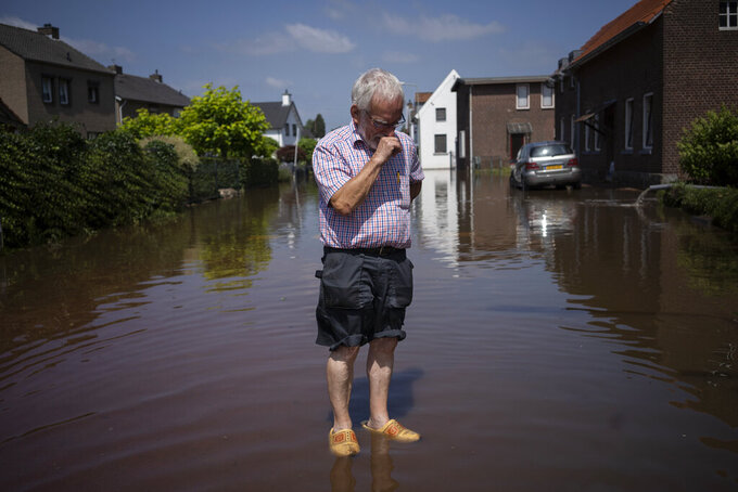 FILE - In this Saturday, July 17, 2021 file photo, Wiel de Bie, 75, stands outside his flooded home in the town of Brommelen, Netherlands. Scientists say there's something different this year from the recent drumbeat of climate weirdness. This summer a lot of the places hit by weather disasters are not used to getting extremes and many of them are wealthier, which is different from the normal climate change victims. That includes unprecedented deadly flooding in Germany and Belgium, 116-degree heat records in Portland, Oregon and similar blistering temperatures in Canada, along with wildfires. Now Southern Europe is seeing scorching temperatures and out-of-control blazes too. And the summer of extremes is only getting started. Peak Atlantic hurricane and wildfire seasons in the United States are knocking at the door. (AP Photo/Bram Janssen, File)