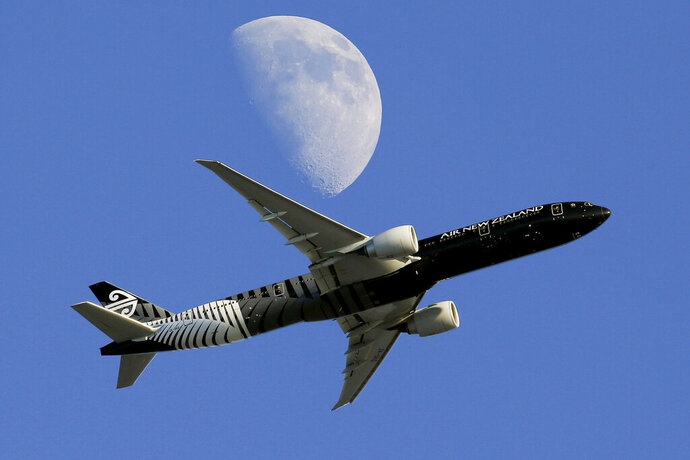 FILE - In this Aug. 23, 2015, file photo, an Air New Zealand passenger plane flies past the moon on its way to the Los Angeles International Airport from London, in Whittier, Calif. New Zealand's national carrier, Air New Zealand, said Thursday, Aug. 22, 2019 that increased fuel costs and engine problems were the main reasons why its annual profit dropped by more than 30%. (AP Photo/Nick Ut, File)