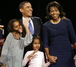 FILE-In this Jan. 3, 2008, file photo, then President-elect Barack Obama, waves to supporters at a caucus rally in Des Moines, Iowa, after winning the Iowa Democratic presidential caucus. Surrounding him is wife Michelle, right, and daughters Malia and Sasha, bottom center. Few states have changed politically with the head-snapping speed of Iowa. (AP Photo/M. Spencer Green, File)