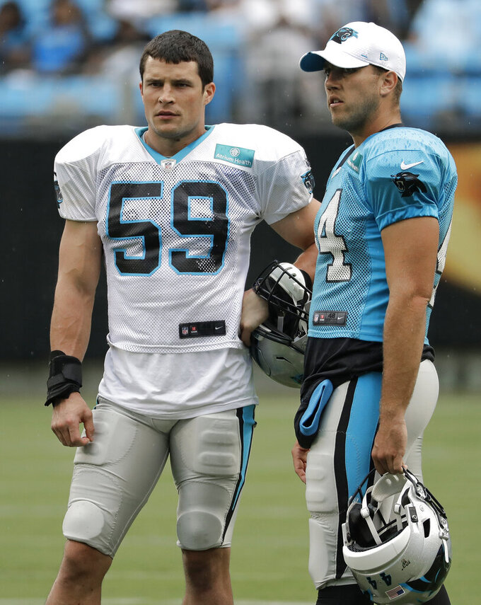 Carolina Panthers' Luke Kuechly (59) and JJ Jansen (44) watch players warm up during a Fan Fest practice at the NFL football team's training camp in Charlotte, N.C., Friday, Aug. 2, 2019. (AP Photo/Chuck Burton)