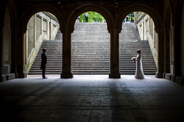 FILE - In this Tuesday, May 23, 2017 file photo, a bride and groom pose for wedding pictures at the Bethesda Terrace in New York's Central Park. Now that most Americans have been ordered to stay at home and avoid nonessential travel to slow the spread of the COVID-19 coronavirus in 2020, many couples — including those who were only days or weeks away from getting married — have had to abruptly postpone their special day, while many others are in limbo, unsure of how to proceed. (AP Photo/Mary Altaffer)