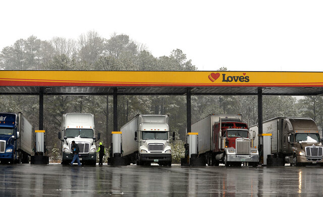 FILE - In this Feb. 11, 2014, file photo, truck drivers stop at a gas station in Emerson, Ga., north of metro Atlanta, to fill up their tractor trailer rigs. The Trump administration eased rules Thursday, May 14, 2020 that limit working hours for truck drivers, and the changes brought immediate protests from labor and safety groups. The Federal Motor Carrier Safety Administration extended the maximum working day for short-haul drivers from 12 hours to 14 hours and applied the longer hours to more drivers by expanding the geographic definition of short-haul driving. (AP Photo/David Tulis, File)
