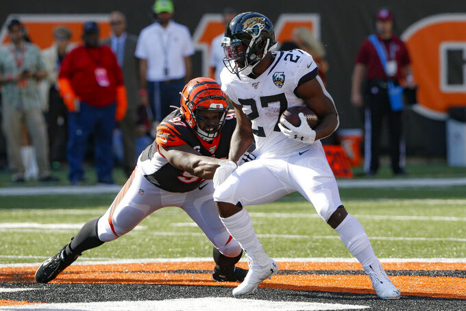 Jacksonville Jaguars running back Leonard Fournette (27) breaks away from Cincinnati Bengals defensive tackle Geno Atkins (97) in the second half of an NFL football game, Sunday, Oct. 20, 2019, in Cincinnati. (AP Photo/Gary Landers)